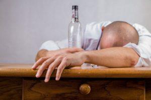 Muž ležící na stole s lahví